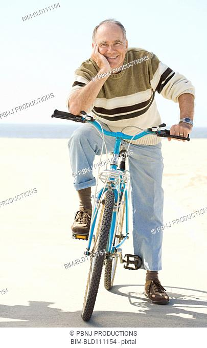 Caucasian older man sitting on bicycle