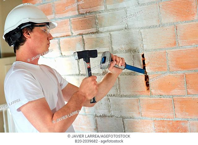 Bricklayer making a groove in the brick wall to place electrical wires. Hammer and chisel hand tools. Construction. Building work. Donostia