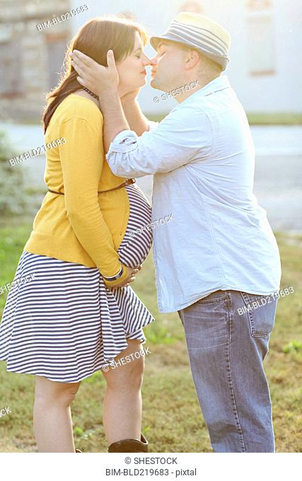 Pregnant couple kissing in sunny field
