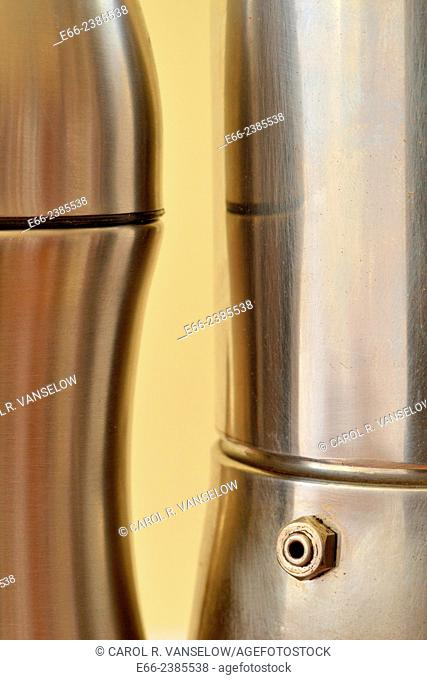 silver aluminium thermos standing next to stainless steel espresso pot