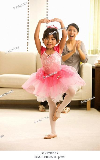 Asian mother watching daughter ballet dancing