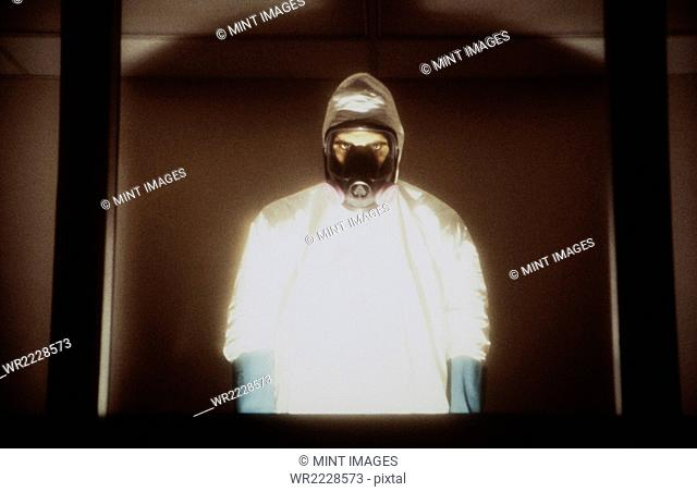A man wearing a hazardous material protective clean suit, a hazmat suit, standing behind window