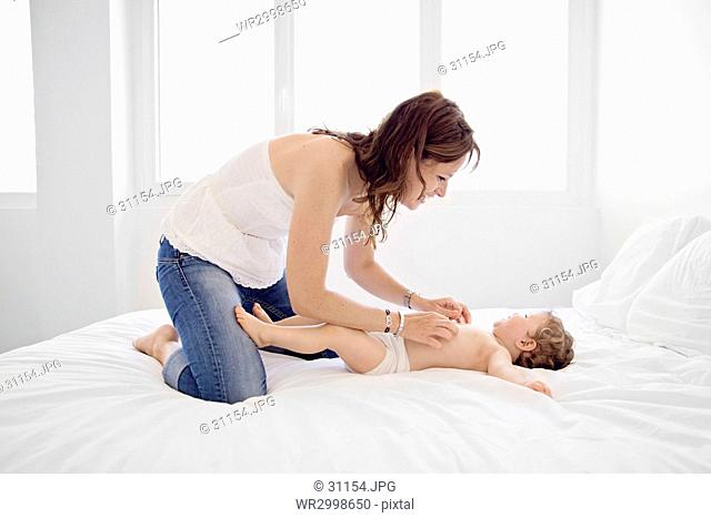 Woman with brown hair wearing jeans kneeling on a bed, tickling young boy
