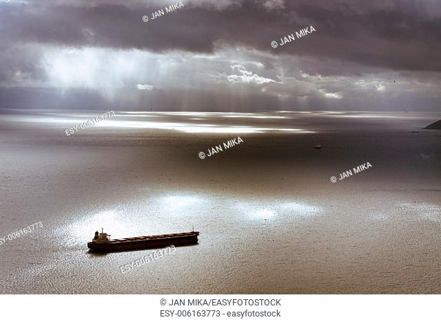 Dramatic dark moody sky and Mediterranean Sea landscape with ship leaving Gibraltar harbor
