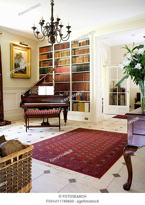 Red oriental rug on cream+black tiled floor in country hall with piano in front of fitted bookshelves