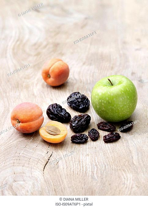 Green apple, apricots and prunes on wooden table