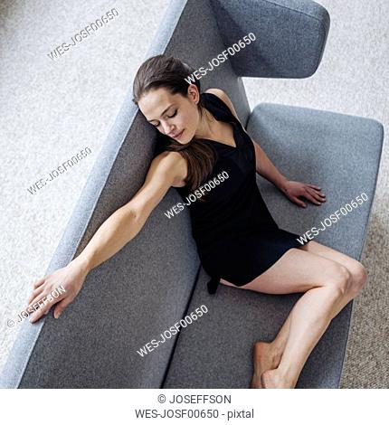 Woman wearing negligee sitting on couch