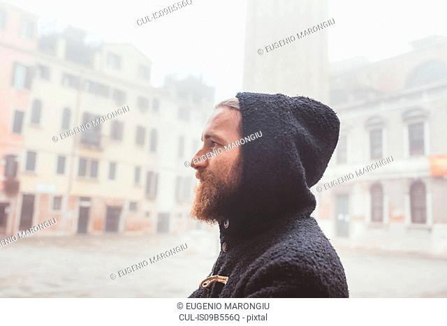 Portrait of man in hood in misty square, Venice, Italy