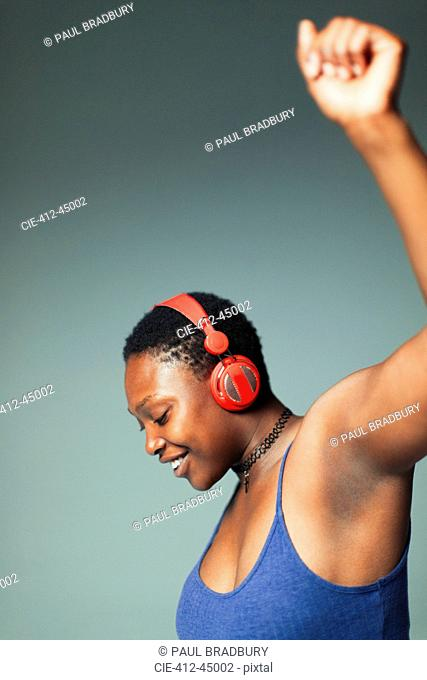 Carefree woman with headphones dancing, listening to music