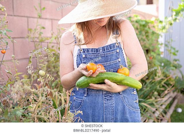 Mixed race farmer gathering vegetables in garden