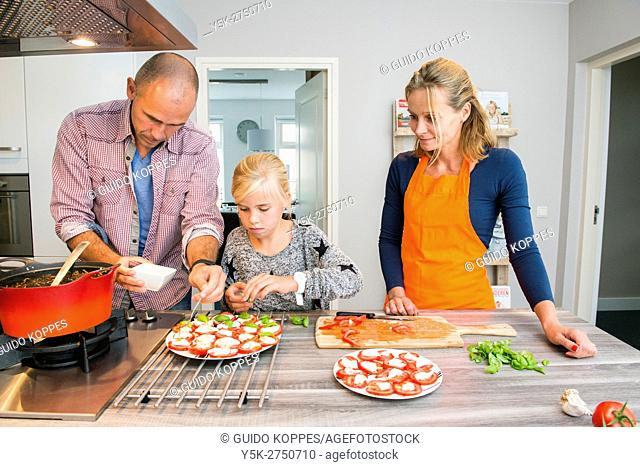 Kaatsheuvel, Netherlands. Mid adult man and woman preparing tomatos for a sidedish with Lasagna, observed and assisted by their young daughter