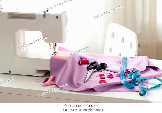 needlework, technology and tailoring concept - sewing machine with scissors, buttons, tape measure and fabric