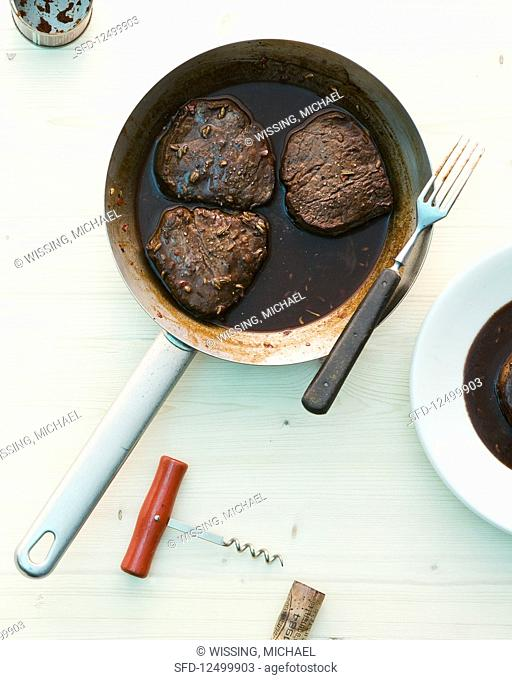 Beef fillet with a red wine sauce in a pan