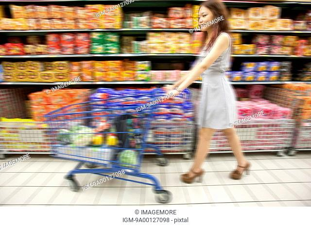 Young woman shopping in supermarket with shopping cart