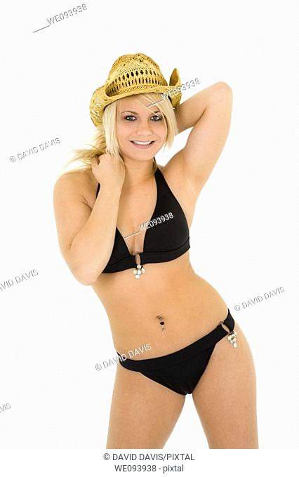 Beautiful and sexy caucasian woman in her early 20s posing in a black bikini on a white background