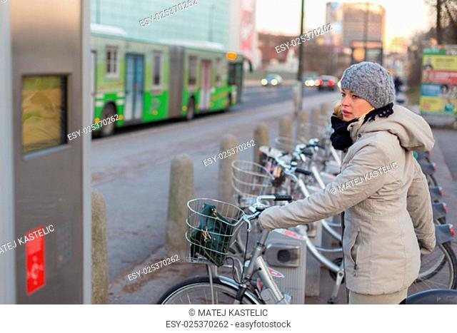 Lady dialing on keyboard of urban bicycle station. Bikes for rent. Green sustainable ecological public transport. Healthy lifestyle