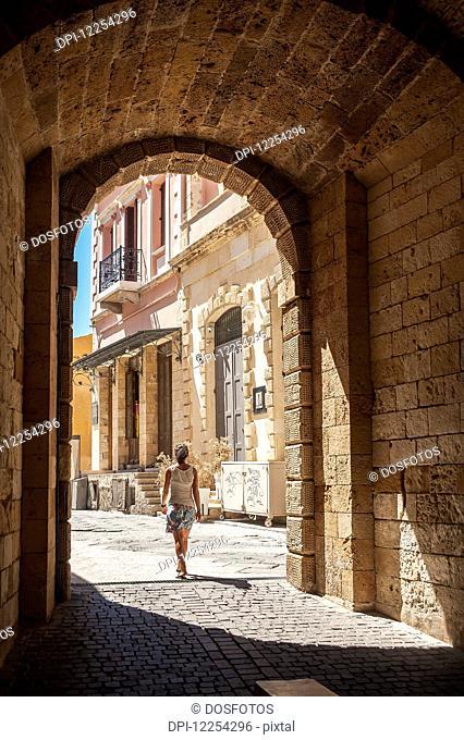 A woman walks through an arched walkway; Chania, Crete, Greece