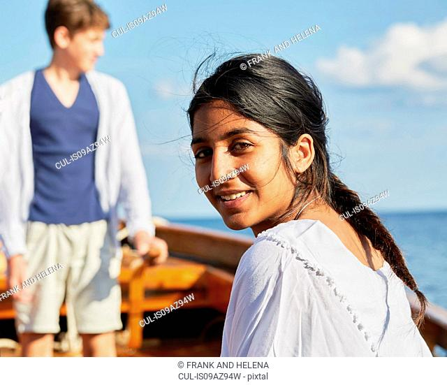 Woman on boat looking over shoulder at camera smiling