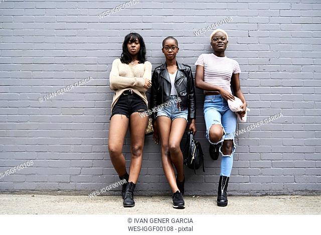 Three friends leaning against grey wall