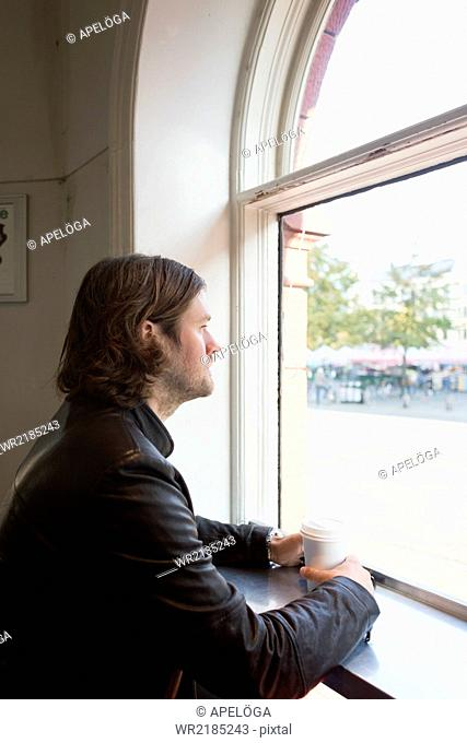 Side view of thoughtful businessman looking out through window in cafeteria