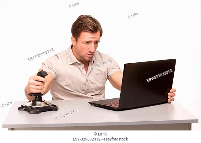 Handsome man playing computer games in the office. Handsome man sitting at the table and looking at the screen