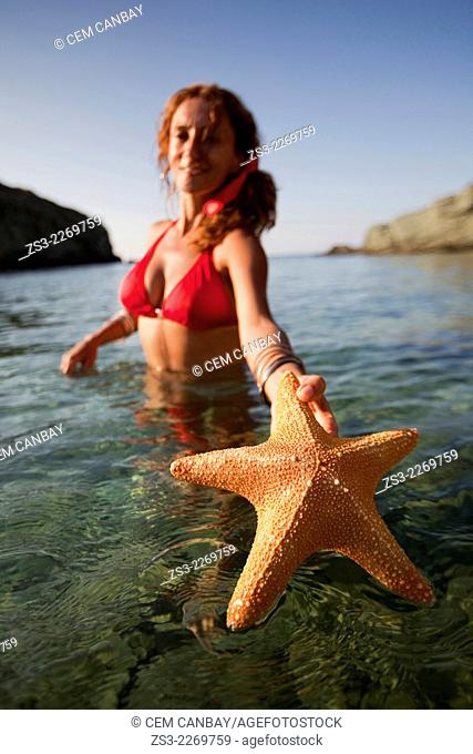 Woman in the sea with a starfish in her hand at Agios Georgios beach, Folegandros, Cyclades Islands, Greek Islands; Greece, Europe