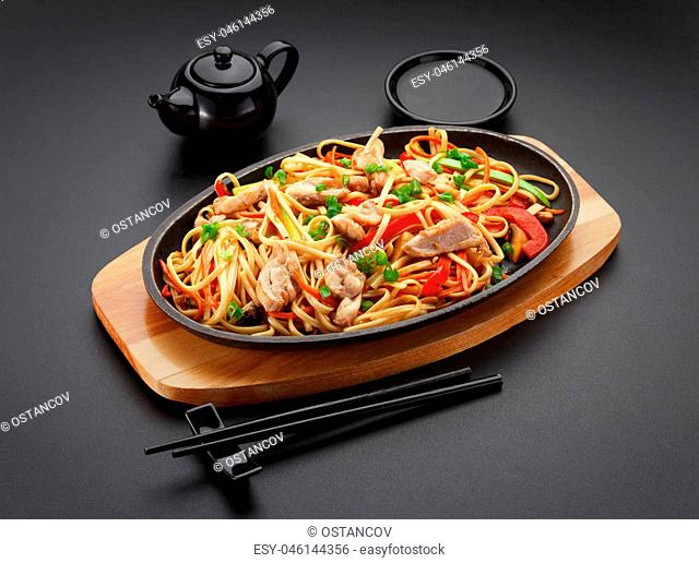 Asia food. Udon noodles with chicken on the black table