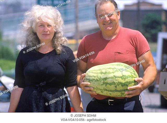 Man and woman walking with watermelon, St. Louis, MO