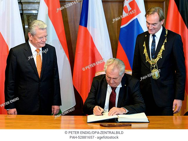 German President Joachim Gauck (L) watches as Czech President Milos Zeman (C) signs the Golden Book of the city of Leipzig next to Leipzig's Lord Mayor Burkhard...