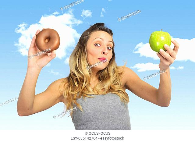 young attractive sport woman holding apple and chocolate donut in her hands in healthy fruit versus sweet junk food dilemma in fitness