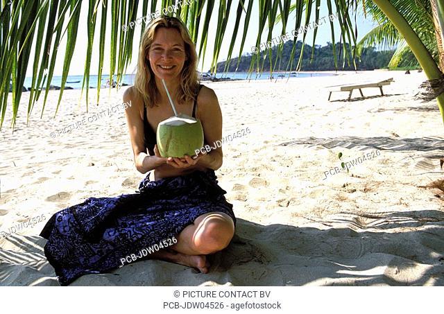 Ngapali Beach, drinking fresh coconut juice under a palm tree