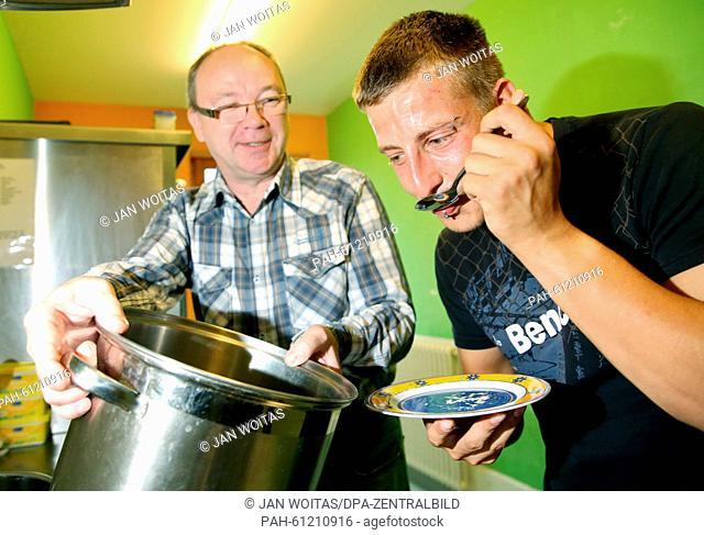 Volunteer helper Uwe Drechsler (l) cooks together with prisoner Bobby Kloeden in the kitchen of the detention centre in Regis-Breitingen, Germany