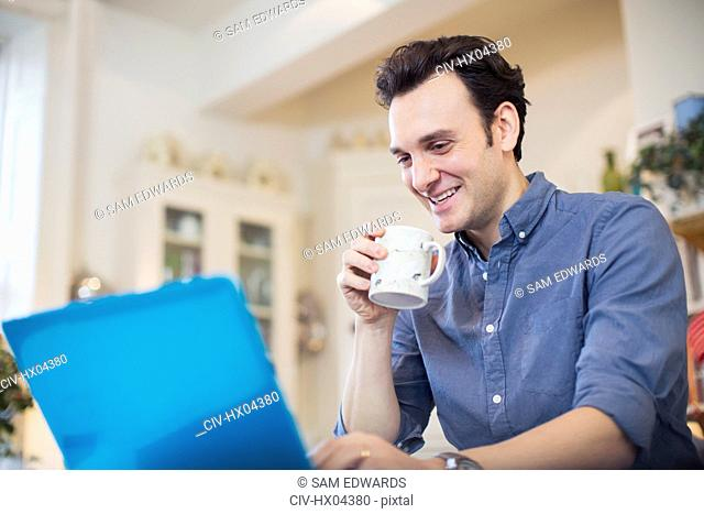 Smiling man drinking coffee, working at laptop