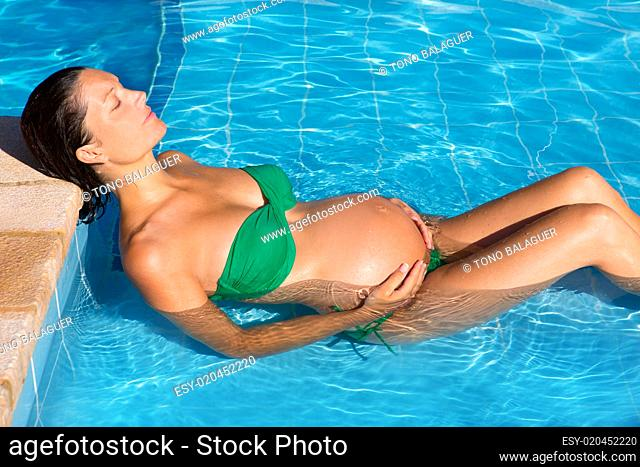 Beautiful pregnant woman sun tanning at blue pool