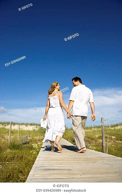 Caucasian mid-adult couple holding hands walking down beach access path