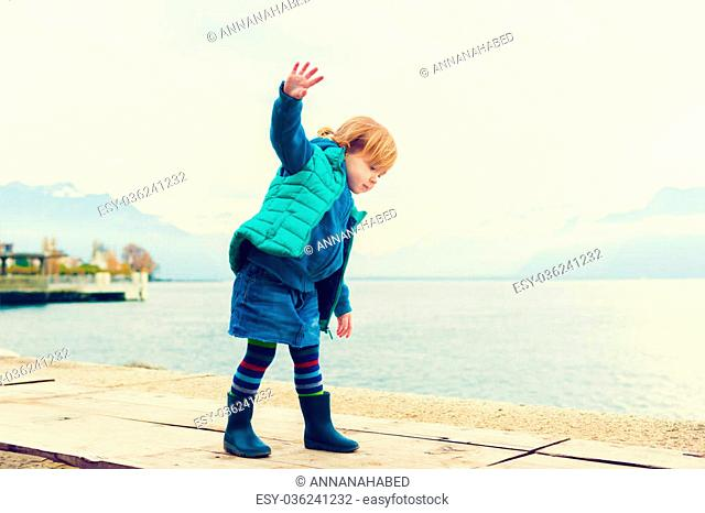 Outdoor portrait of adorable toddler girl of 2 years old, wearing green waistcoat, denim skirt and blue rain boots