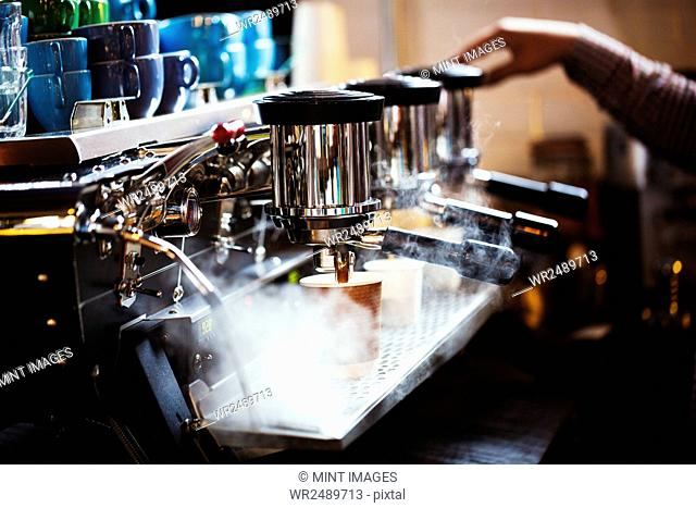 Specialist coffee shop. A person working at a large coffee machine, with three percolating containers, handles and a pipe sending out steam