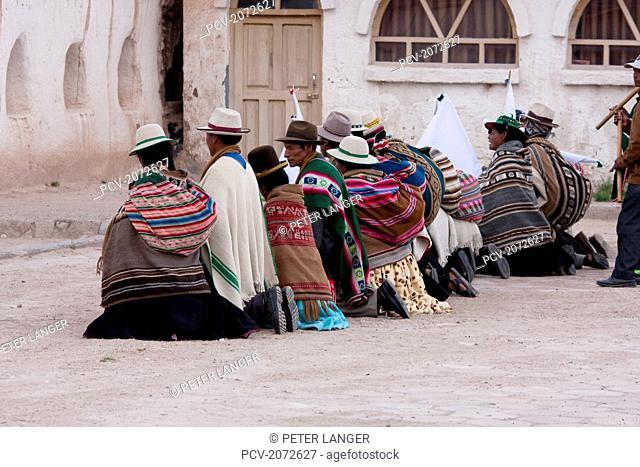 Aymara Elders Kneeling In Front Of The Santiago De Curahuara De Carangas Church During Carnival, Curahuara De Carangas, Oruro, Bolivia