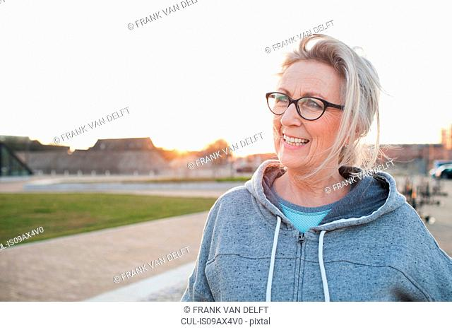 Portrait of woman wearing eyeglasses and hooded top looking away smiling