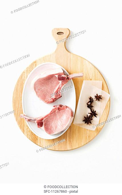 Pork chops and star anise on a chopping board