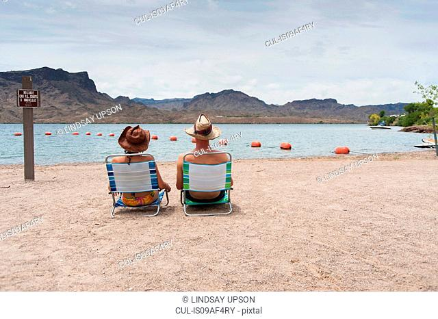 Couple sitting on deck chairs, Lake Havasu, Arizona, USA