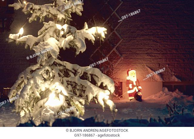 Snow covered Christmas tree and lighted plastic Santa Claus. Sweden