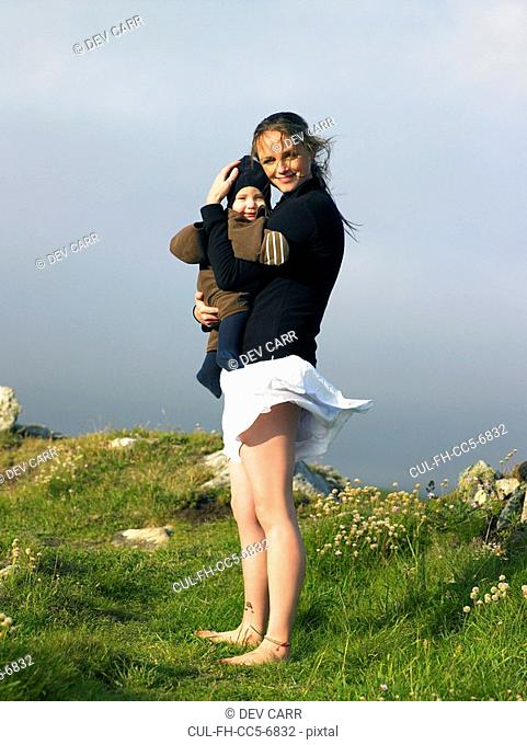 Young woman holding baby with the wind blowing her skirt