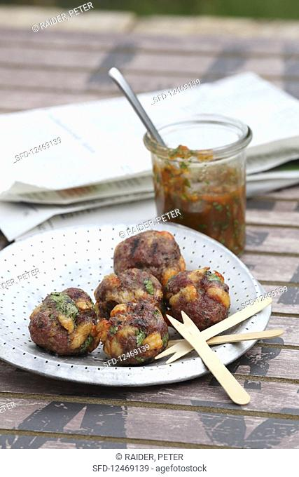 Grilled minced meat and shrimp balls with a tomato dip