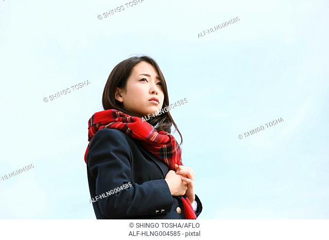 Japanese high-school student with scarf against blue sky