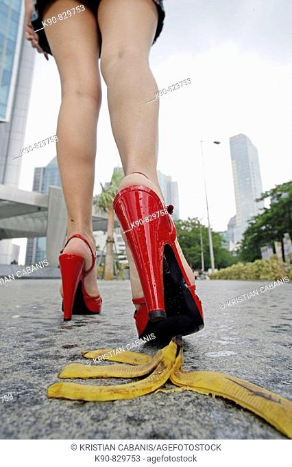 Young lady, nearly stepping with her red high heels of the peel of a banana, but luckily she did not, Jakarta, Indonesia, Southeast Asia