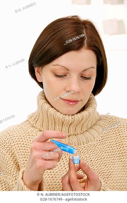 Young woman in a beige turtleneck pullover, counting homeopathic pills out of a blue tube