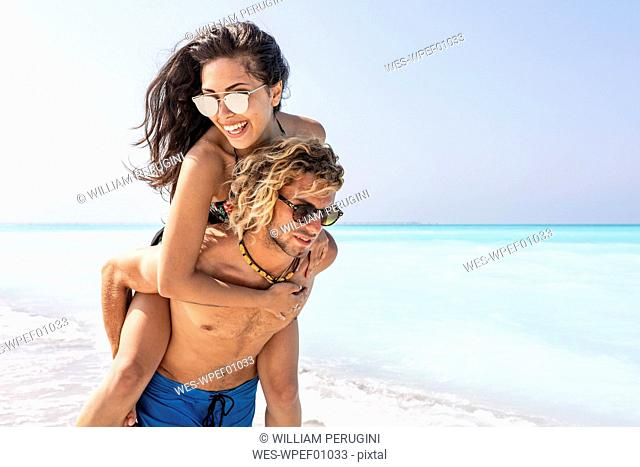 Happy couple on gthe beach, man carrying girlfriend piggyback