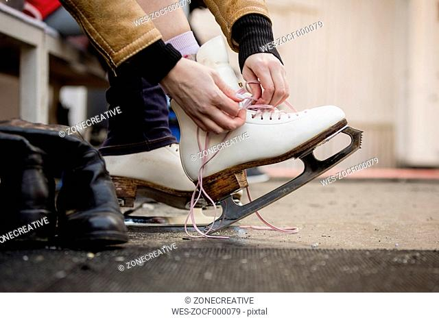 Close-up of woman putting on ice skates