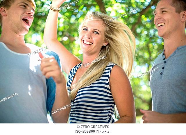 Three young adult friends dancing together at beach party